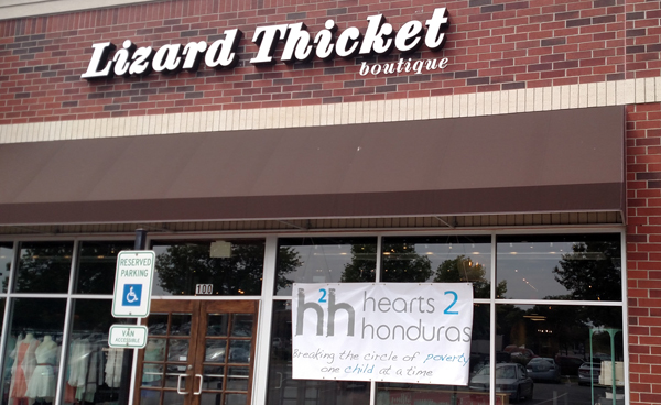 An exterior shot of a Lizard Thicket store with a banner advertising the Hearts 2 Honduras fundraiser.