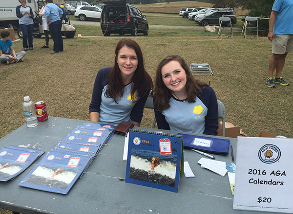 Two Lizard Thicket employees man a booth selling calendars for Adopt a Golden Atlanta.
