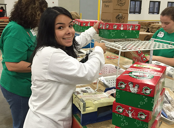 A Lizard Thicket employee packing shoe boxes for Operation Christmas Child.