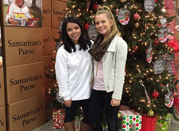 Two Lizard Thicket employees pose in front of the Samaritan's Purse Christmas tree.