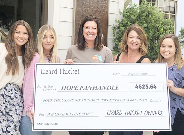 Image of Lizard Thicket employees presenting a check to Hope Panhandle.